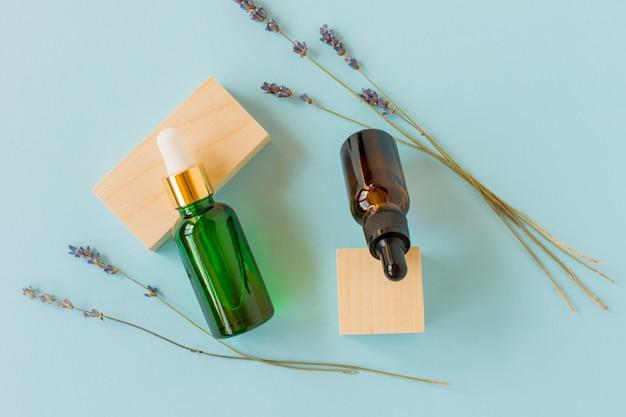 나무 큐브가 있는 파란색 배경에 스포이드와 라벤더 가지가 있는 에센셜 오일. 갈색과 녹색 유리 화장품 병, 혈청.