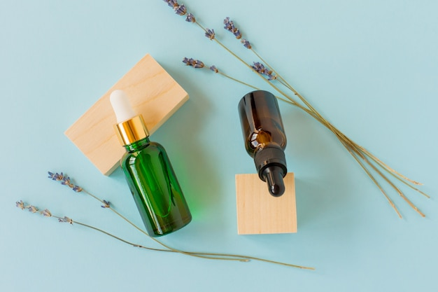Essential oil with a dropper and lavender branches on a blue background with wooden cubes. brown and green glass cosmetic bottle, serum.