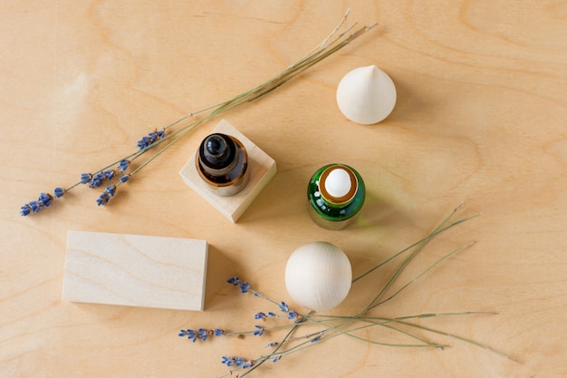 Essential oil with a dropper and lavender branches on a wooden background with wooden cubes. brown and green glass cosmetic bottle, serum. top view.
