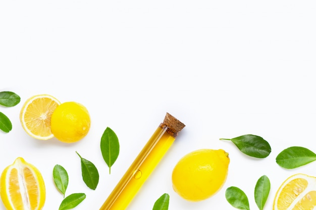 Essential oil with fresh lemon and green leaves on white