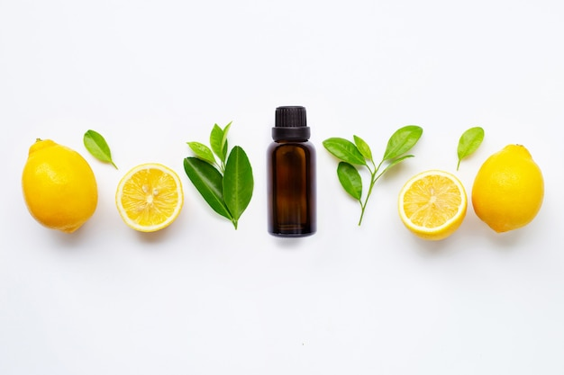 Essential oil with fresh lemon with leaves isolated