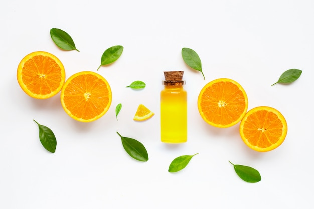 Essential oil with fresh orange citrus fruit with leaves isolated on white