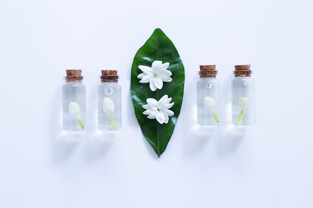Essential oil with jasmine  flower on over white