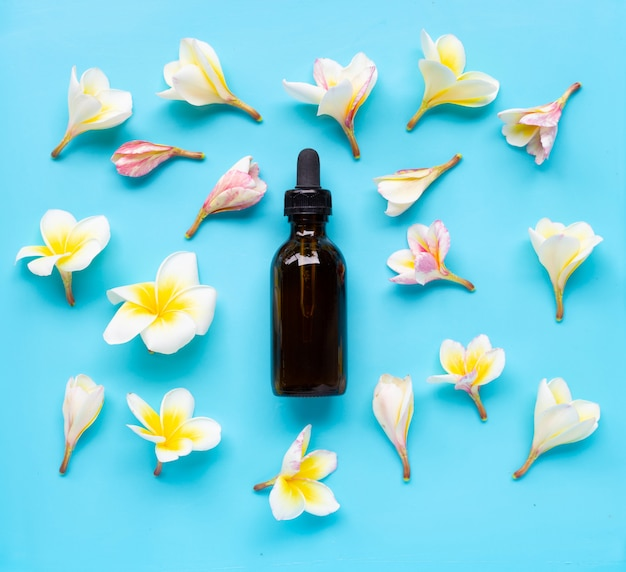 Essential oil with plumeria or frangipani flower on blue