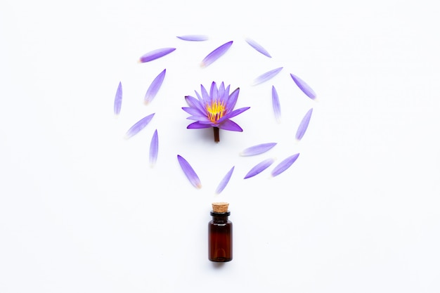 Essential oil with purple lotus flower on white.