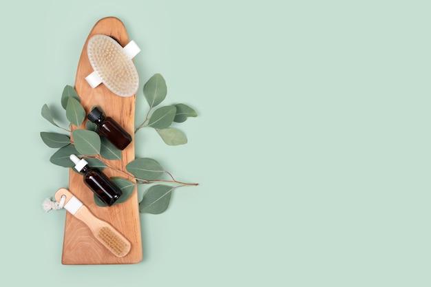 녹색 배경에 천연 유칼립투스 잎 에센셜 오일과 마사지 브러쉬