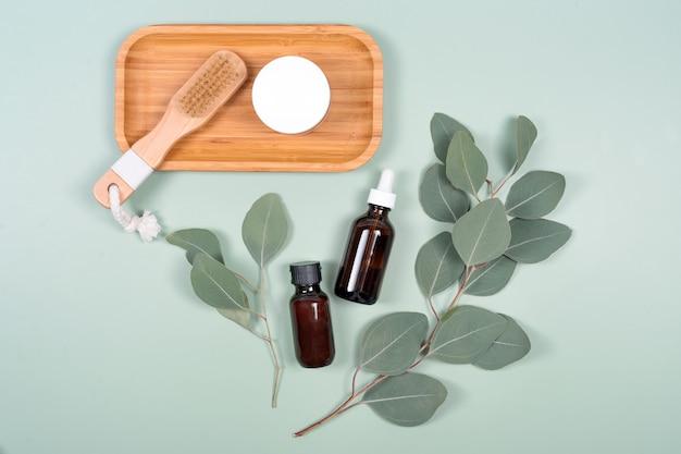 녹색 배경에 천연 유칼립투스 잎이있는 에센셜 오일, 페이셜 크림 용기 및 마사지 브러시