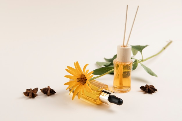 Essential oils and flower on plain background