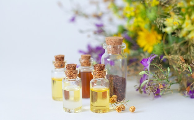 Эфирные масла в стеклянных бутылках с органическими целебными травами и цветами на светлом фоне