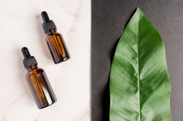 Essential oils with drops pipette and cream on marble background.