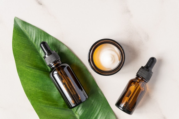 Essential oils with drops pipette and cream on marble