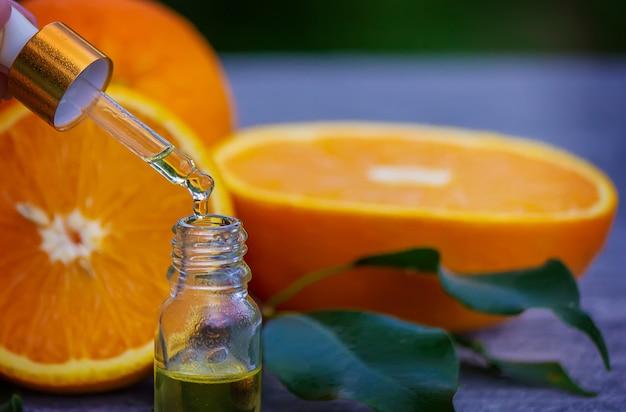 병에 담긴 에센셜 오렌지 오일, 표면에 신선한 과일 조각