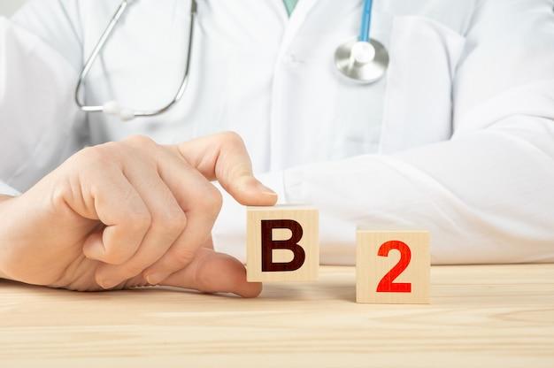인간을위한 필수 비타민과 미네랄. 나무 큐브에 b2 알파벳입니다. b2 비타민-건강 개념.