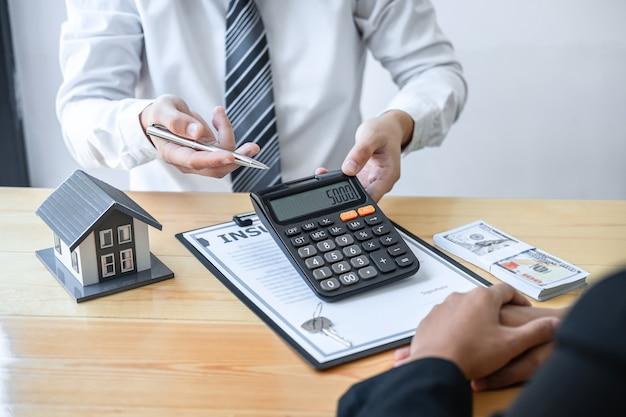 不動産業者は、承認された申請書、住宅保険、不動産投資のコンセプトとの契約書について話し合い、署名した後、住宅ローンを提示し、クライアントに家を提供しています。