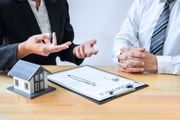 Estate agent are presenting home loan and giving house to client after signing agreement