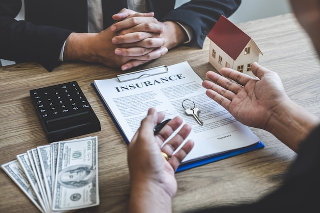 Estate agent broker reach contract form and presentation to client signing agreement contract real estate with approved mortgage application form, buying mortgage loan offer for and house insurance
