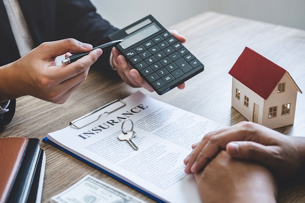 Estate agent broker reach contract form and presentation to client signing agreement contract real estate with approved mortgage application form, buying mortgage loan offer for and house insurance.