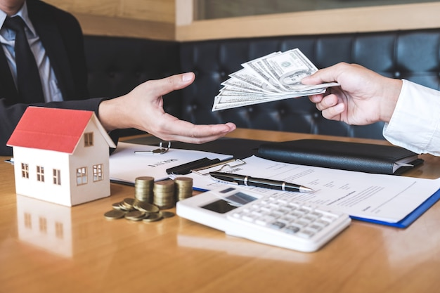 Estate agent broker receive money from client after signing agreement contract real estate with approved mortgage application form, buying or concerning mortgage loan offer for and house insurance
