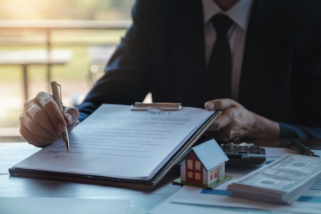 Estate agent gives pen and documents agreement with customer to sign contract.
