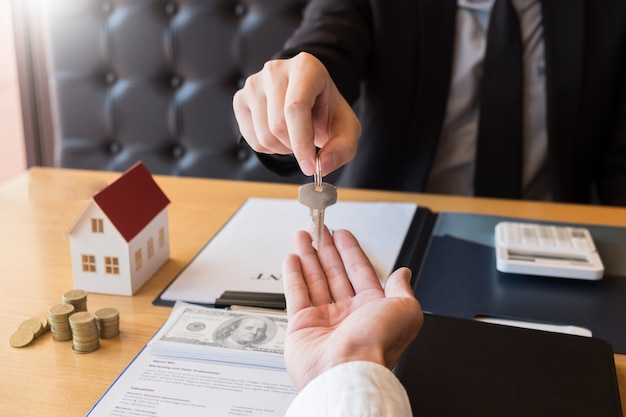 Estate agent giving house key customer sign agreement property