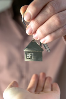 Estate agent giving house keys to client for new home, contract real estate for mortgage approved, focus on keys, business, financial, estate concept