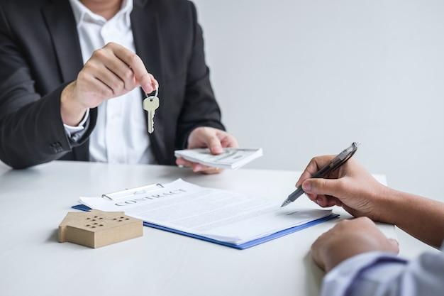 Агент по недвижимости дает ключи от дома клиенту после подписания договора подряда недвижимости с утвержденным