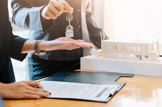 Агент по недвижимости дает ключи от дома человеку и подписывает соглашение в офисе