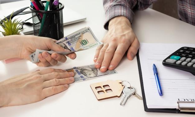 女性に家の鍵を与え、オフィスで契約書に署名する不動産業者