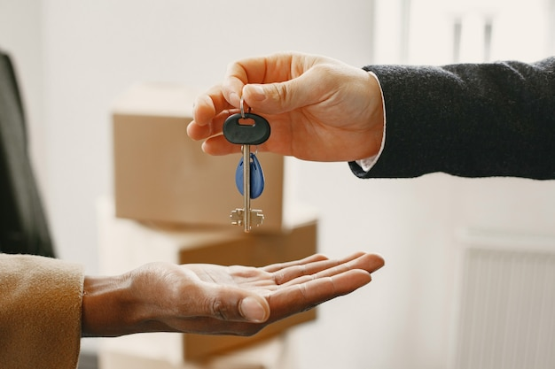 Estate agent giving keys from apartment to newlyweds, couple buying house.