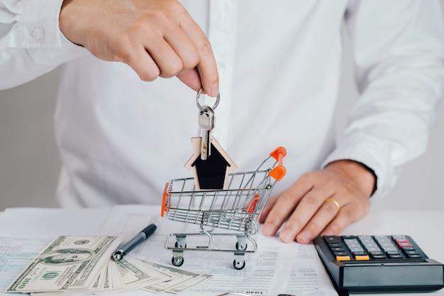 ショッピングカートに家の鍵を持っている不動産業者の手。不動産業者。不動産取引のアイデア