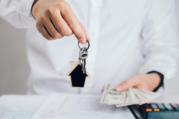 Агент по недвижимости рука ключи от дома с банкноты. концепция ипотеки. недвижимость, переезд или сдача в аренду.