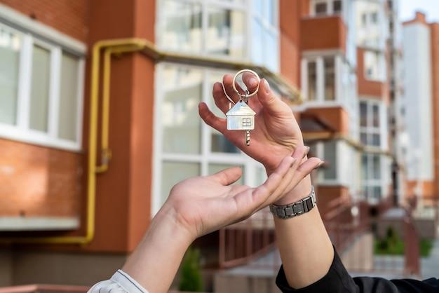부동산 중개인이 집에있는 새 소유자의 집 열쇠를 전달합니다. 집 판매 또는 임대