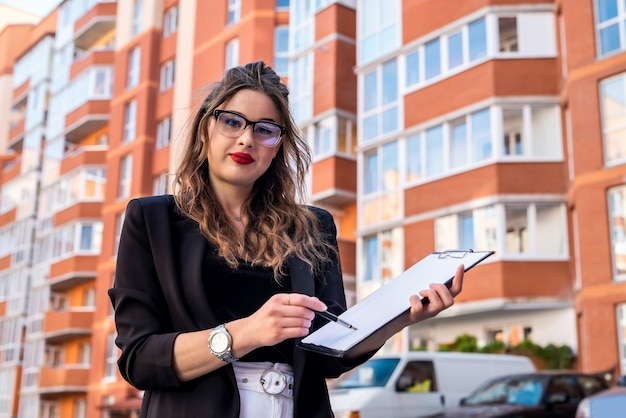 Estate agent holding clipboard near new house. sale or rent new apartment