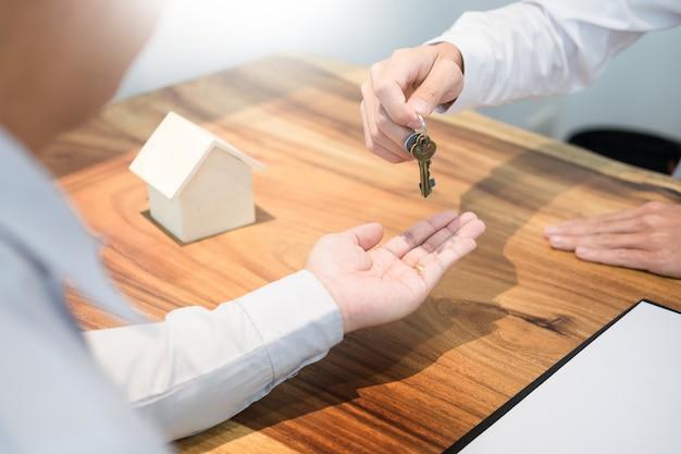 Агент по недвижимости в костюме, сидящий в офисном столе. передача ключей от дома с клиентом.