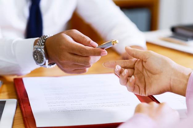 Агент по недвижимости предлагает ручку