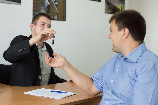 不動産業者または自動車販売員が取引を完了し、オフィスで新しい購入者に鍵を渡します