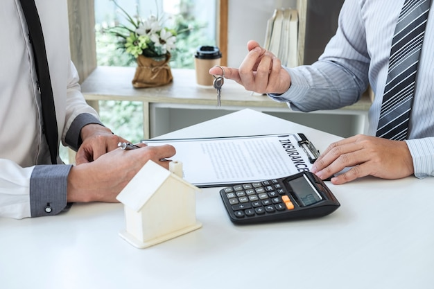 Estate agent presenting home loan and giving keys to customer