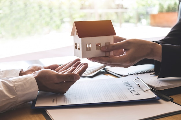 Estate agent sending house model to client after signing agreement contract real estate with approved mortgage application form, concerning mortgage loan offer for and house insurance