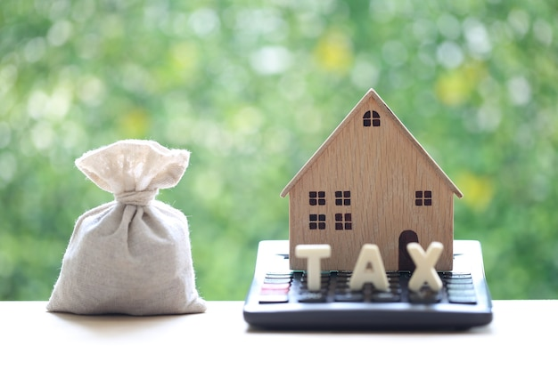 Estate tax,model house on calculator with money bag on natural green background, business investment and save money for prepare in future concept