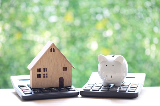 Estate tax,model house and piggy bank on calculator with on natural green background,business investment and save money for prepare in future concept