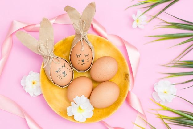 ピンクの机の上の木製のカップにウサギのように描かれたエステルの卵