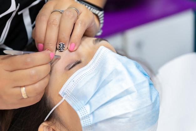 Работник-косметолог поправляет брови клиента, обе с маской
