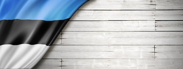Флаг эстонии на старой белой стене. горизонтальный панорамный баннер.