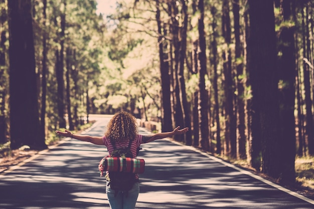 Eternity and success satisfaction life concept with lonely girl curly hai rin the middle of long road in the forest with open arms and backpack - wanderlust and travel style people
