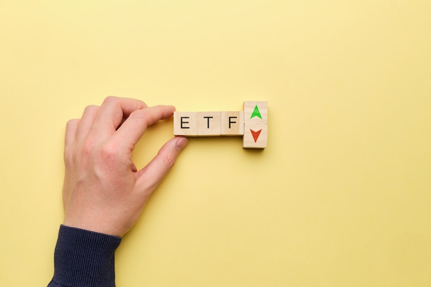 Etf concept with up and down arrows on yellow background.