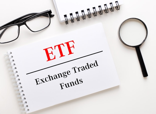 Etf exchange traded funds is written in a white notebook on a light background near the notebook, black-framed glasses and a magnifying glass