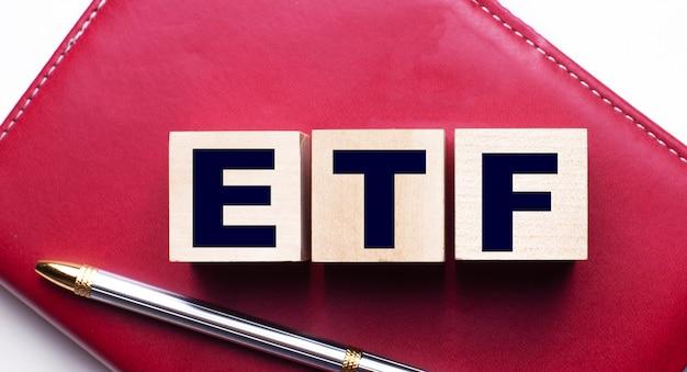 Etf上場投資信託は、ペンの近くのバーガンディのノートに立つ木製の立方体で構成されています。ビジネスコンセプト