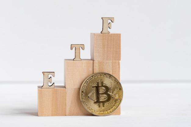 ビットコインコインの横にある木製のetf文字。