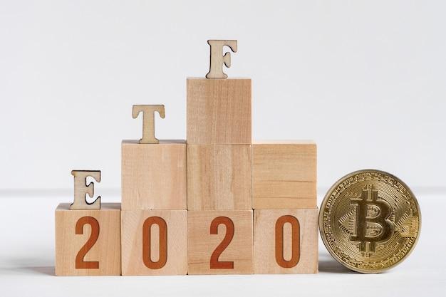 Etf буквы сделаны из дерева рядом с биткойн монеты.