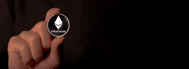 Сияющая серебряная монета эфириума в мужской руке крупным планом над черным знаменем с местом для текста